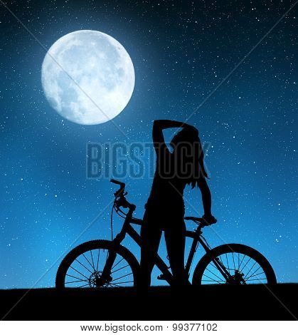 Girl on a bicycle in night sky.