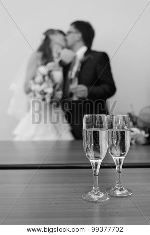 Young caucasian couple wedding portrait. Focus on glasses with champagne.