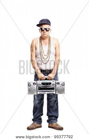 Full length portrait of a hardcore rapper holding a ghetto blaster and looking at the camera isolated on white background