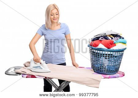 Young blond woman ironing clothes on an ironing board isolated on white background