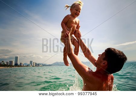 Father Tosses Up Laughing Little Daughter Above Sea Water