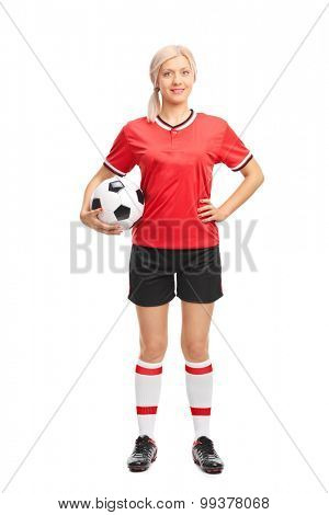 Full length portrait of a young female football player in a red jersey holding a football and looking at the camera isolated on white background