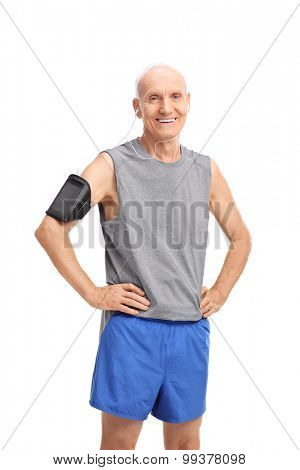 Studio shot of a senior man in sportswear listening to music on his cell phone and looking at the camera isolated on white background