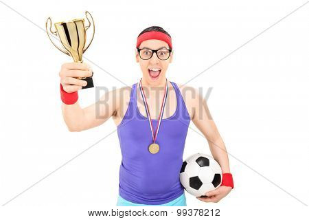 Nerdy young football player holding a gold cup in one hand and a football in the other isolated on white background