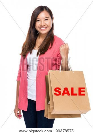 Happy woman with shopping bag and showing a word sale