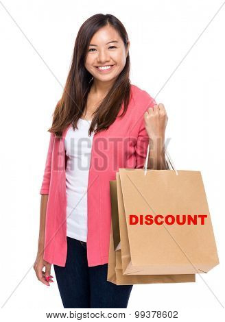 Happy woman with shopping bag and showing a word discount