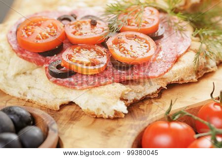 sandwich with pita bread salami and vegetables on wood table