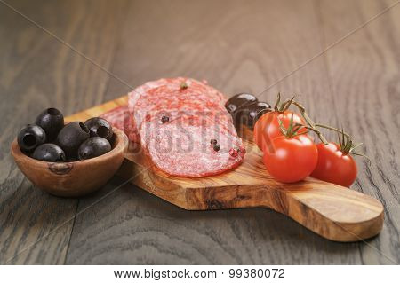 antipasti with salami olives and tomatoes on wood table