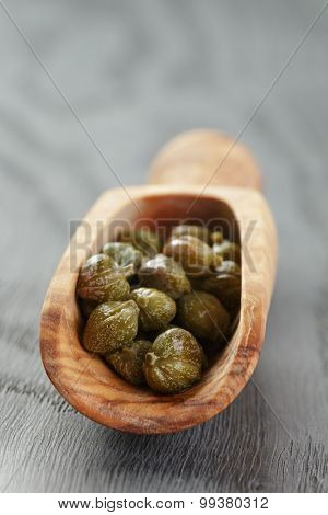 marinated capers in wood scoop on table