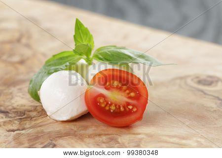 small balls of mozzarella with basil leaves ant tomato