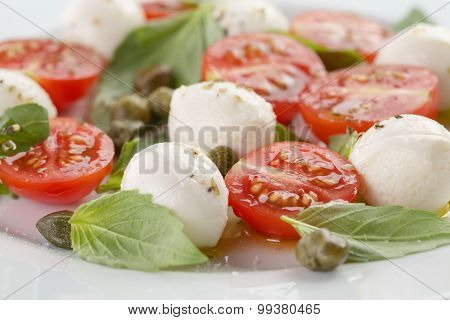 caprese salad with mini mozzarella balls, tomatoes and capers