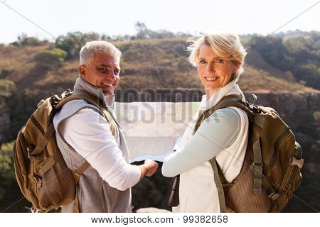 happy middle aged couple with map looking back