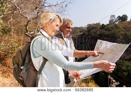active senior hikers on top the mountain pointing at map