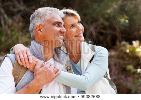 lovely senior couple daydreaming in forest