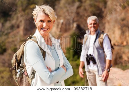 senior female hiker standing on mountain with husband on background