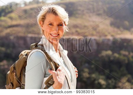 happy mid age woman with backpack standing on top of the mountain