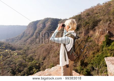 senior woman standing on top of the mountain and using binoculars