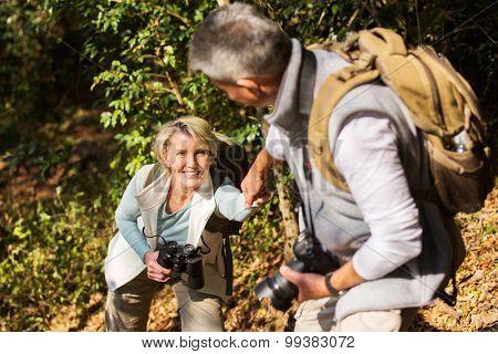 caring man helping his wife climbing mountain