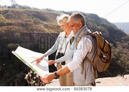 active middle aged hikers looking at a map on top of the mountain