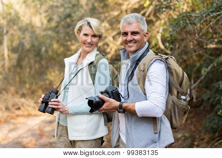 active mature couple in forest looking at the camera