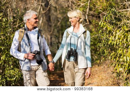happy mature couple hiking in mountain