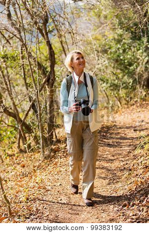 active senior woman hiking in forest with dslr camera