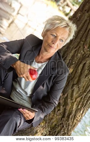 Business Woman Sitting On A Tree And Eating An Apple