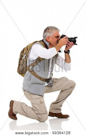 male tourist on his knee taking pictures on white background