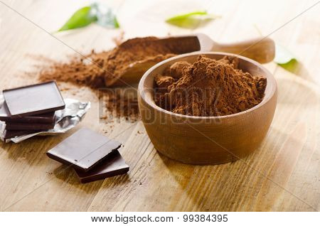Chocolate Bars With A Wooden Bowl Of Cacao Powder.