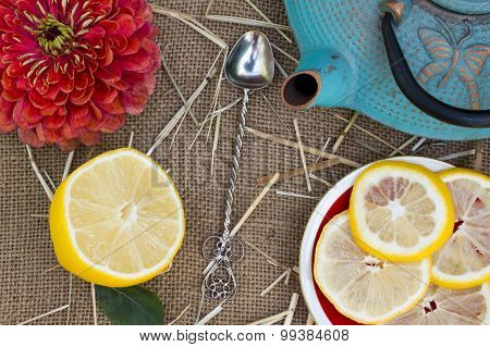 Shot From The Dry Black Tea With Flowers , A Teapot On Burlap Background