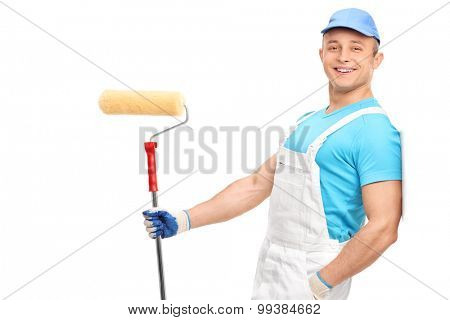 Relaxed young painter in a white jumpsuit holding a paint roller and leaning against a wall isolated on white background