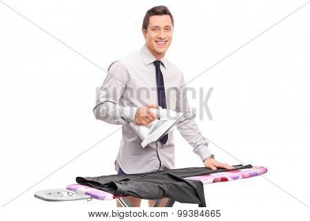 Young man ironing his pants and looking at the camera isolated on white background