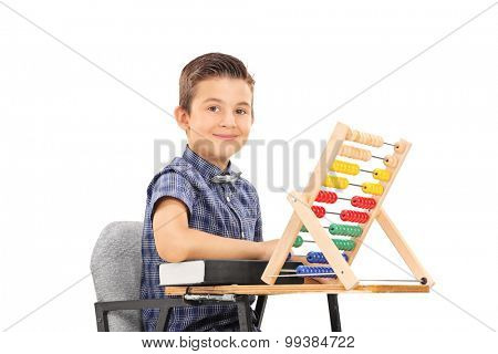 Cute little schoolboy sitting at a school desk with a book and an abacus on it isolated on white background