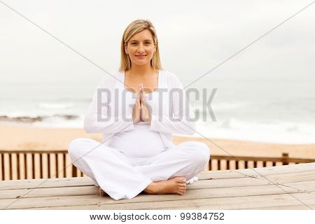 pretty pregnant woman meditating outdoors