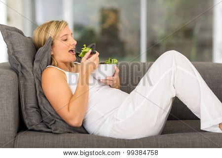 relaxed pregnant woman eating green salad at home