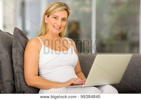happy young pregnant woman with laptop at home