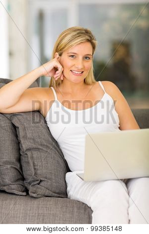 portrait of pretty young pregnant woman at home using laptop