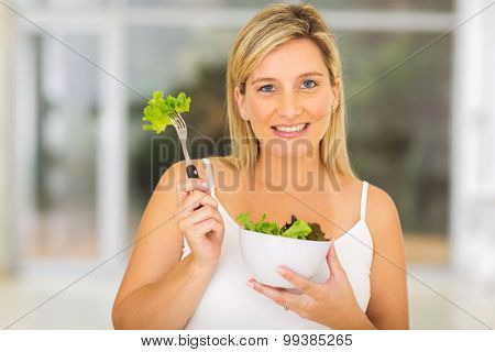 portrait woman with fresh green salad at home
