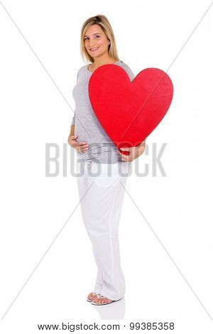 portrait of pregnant woman holding red heart against white background