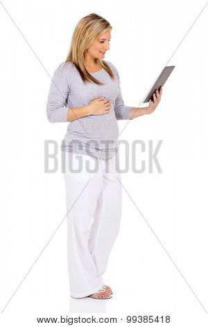 side view of pregnant woman using tablet computer on white background