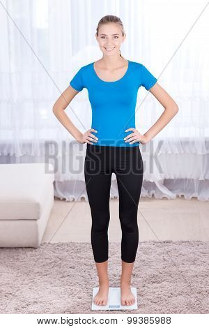 Smiling young woman measuring weight