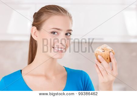Upbeat girl holding muffin