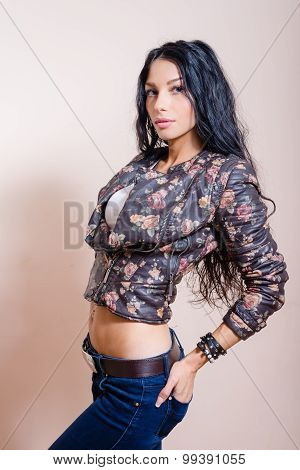 Young pretty brunette with long hair in leather jacket and belly top