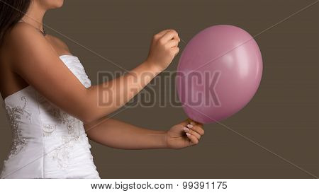 Bride In Wedding Dress Lets A Balloon Burst With A Needle