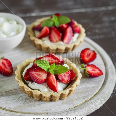 Tartlets With Cream And Strawberries, Decorated With Mint Leaves On Wooden Surface
