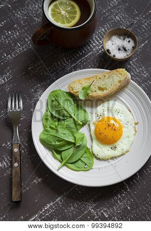 Fried Egg And Fresh Spinach On A White Plate On A Dark Background