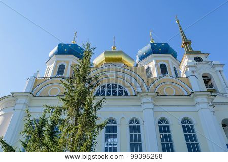 Facade And Upper Part Of Church With Three Blue And Gold Domes And Bell Tower Against Cloudless Sky