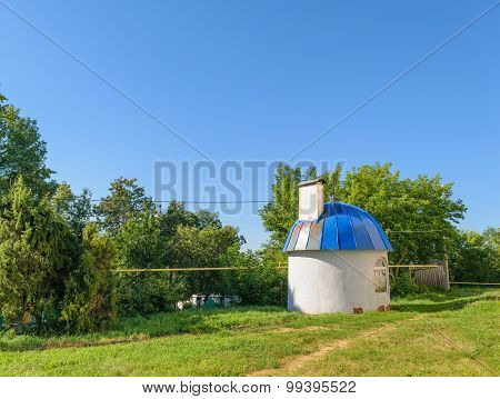 Small Round House With Blue Domed Roof On Green Lawn On Sunny Summer Day