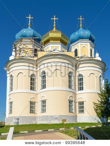 Church With Three Blue And Golden Domes Against Blue Cloudless Sky On Sunny Summer Day