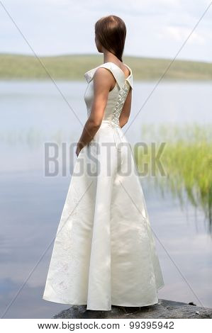 Girl In A White Dress Standing On A Rock Against The Backdrop Of The Lake